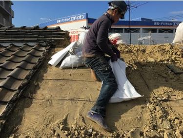 劣化した屋根瓦をはいだ後下地の土を集めて土嚢に詰め廃棄する