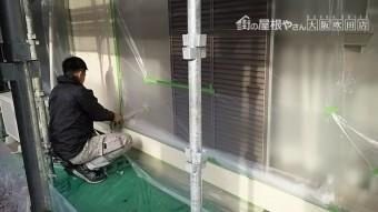 外壁にマスカーを使用し、塗装しない箇所を養生