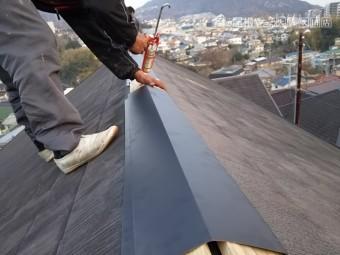 新しいシルバーブラックの棟板金を施工しています。