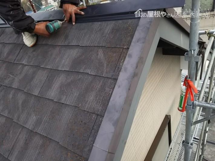シルバーブラックの棟板金を横からビス打ち