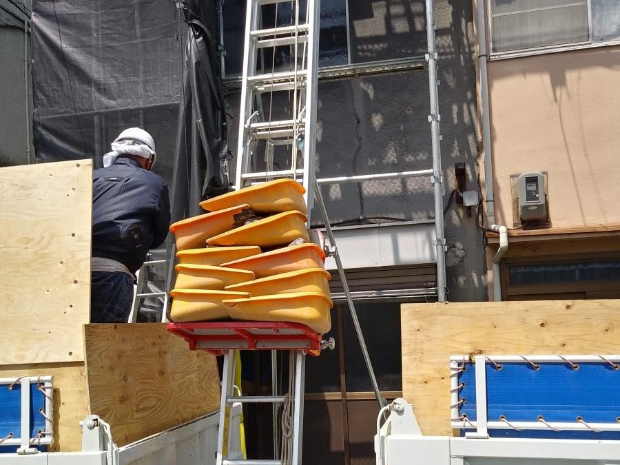 梯子を使用して廃材を運び出しています