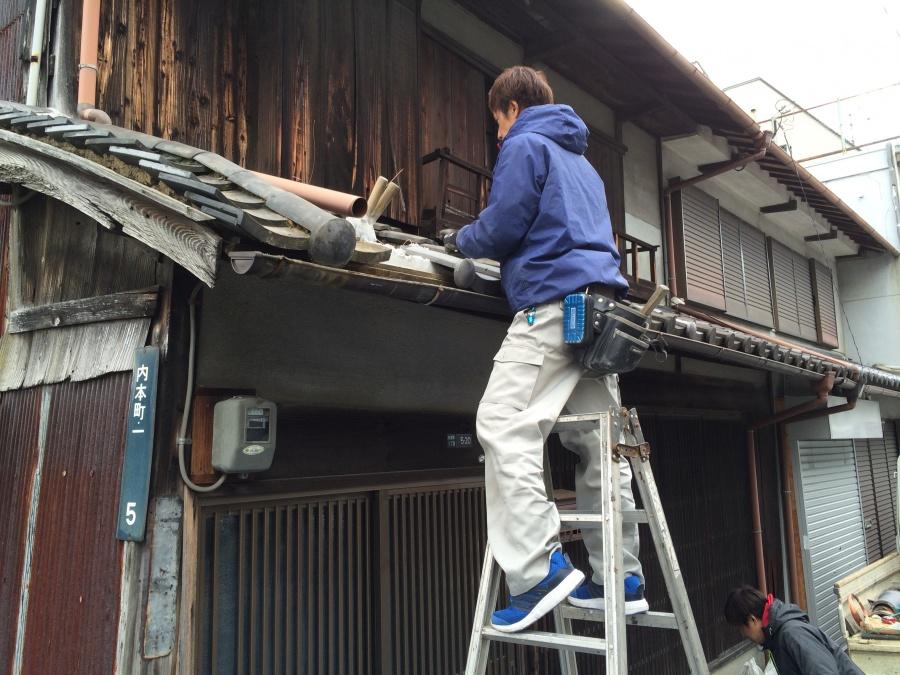 差掛け屋根の瓦の葺き替えをする脚立に乗った職人