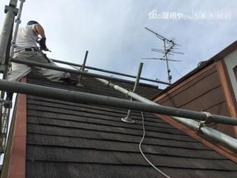 スレート屋根補修工事のために足場を組む職人