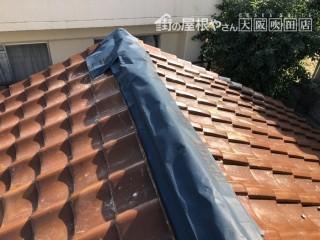台風の強風で崩壊した棟を粘着シートでカバー