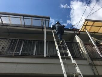 三連梯子で屋根に登っています。