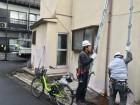 吹田市長屋造りの瓦屋根補修工事現場にて外壁をチェックする職人