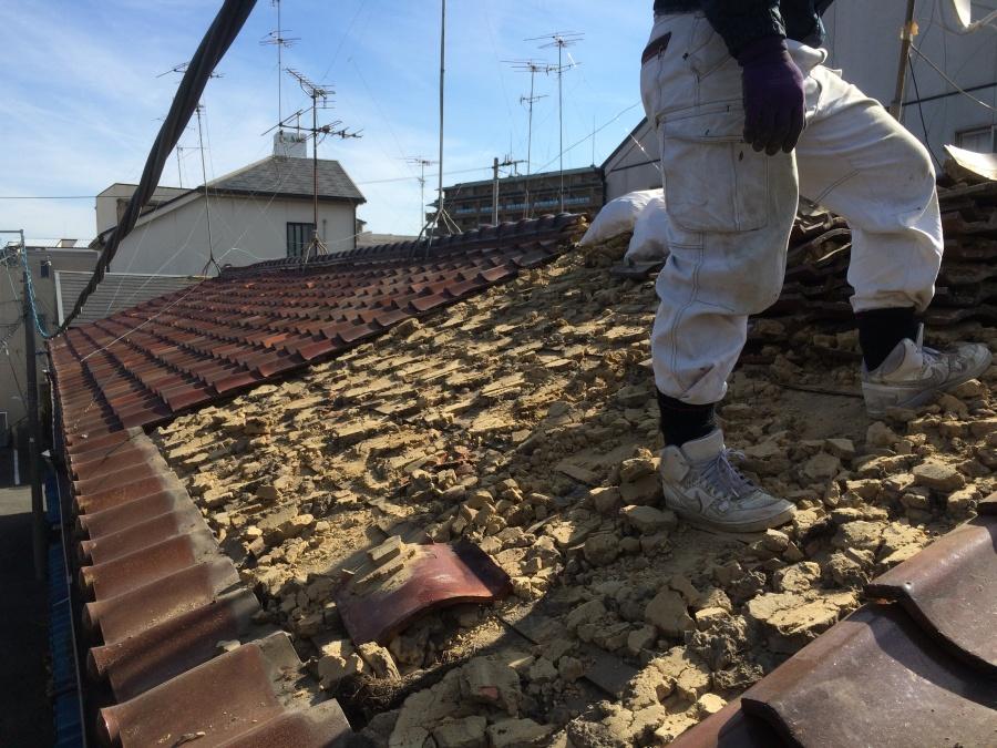 長屋の一部の劣化した瓦屋根を剥いでいく職人