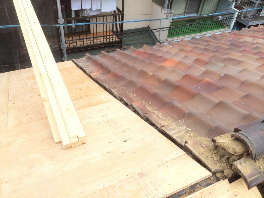 長屋の一部の劣化した瓦屋根を取り除き野地板を張ったところとの境目