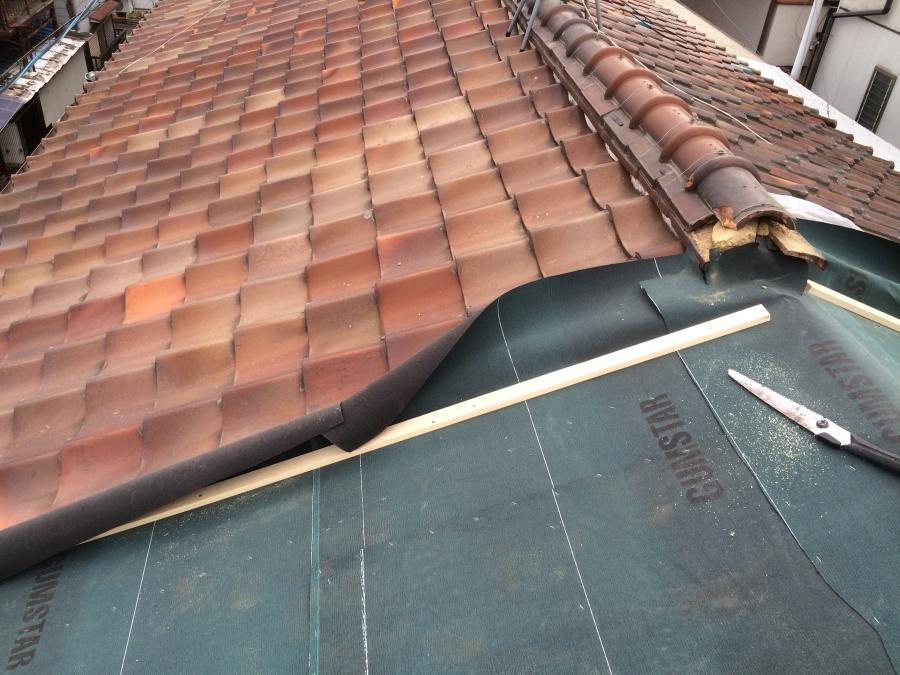 長屋の劣化した瓦屋根の一部を剥ぎルーフィングシートという防水シートを張ったところ