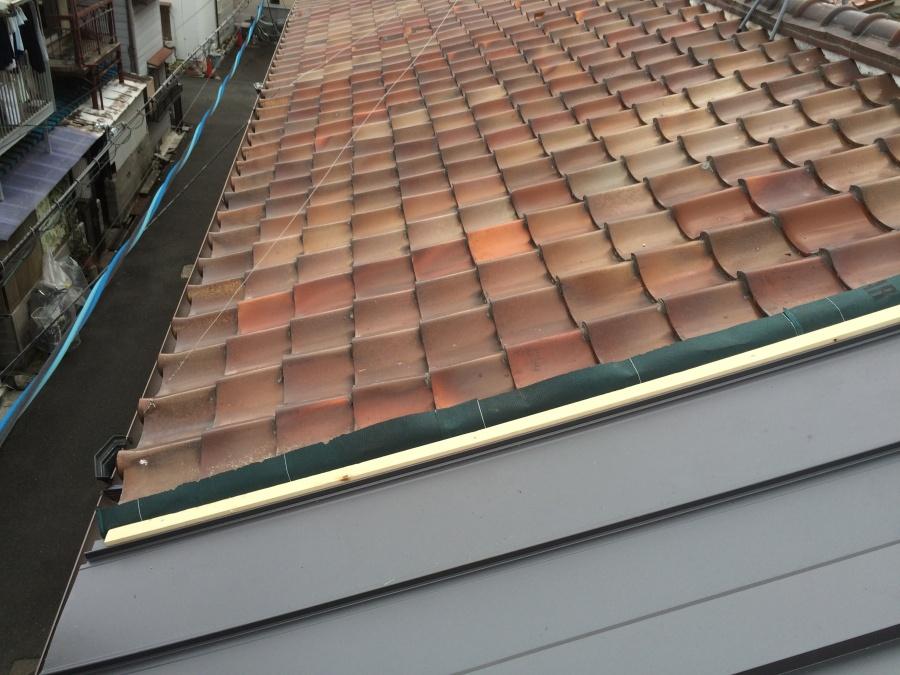 長屋の劣化した瓦屋根の一部を剥ぎ金属屋根の立平葺きで施工したところ