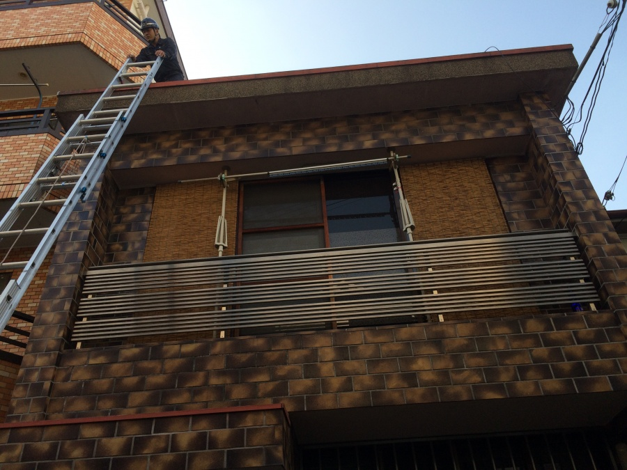 梯子で屋根調査に上がる職人