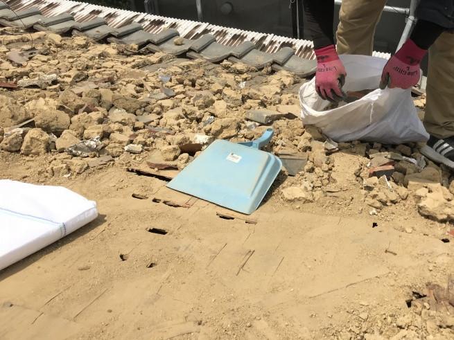 屋根に葺かれた大量の葺き土を撤去中