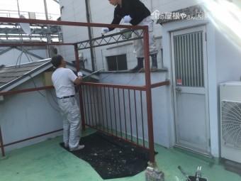 屋上鉄柵に錆止め塗装をする職人