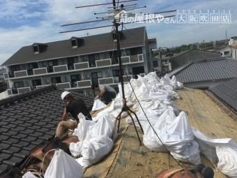 屋根の土を土嚢に入れる