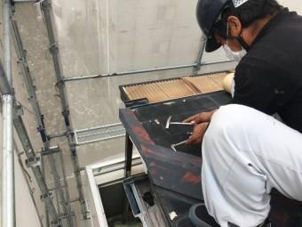 屋根の古い板金を撤去する職人