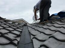 瓦屋根に上って現地調査のため写真を撮る職人