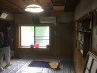 バケツやシートで応急処置された雨漏りのひどい居室