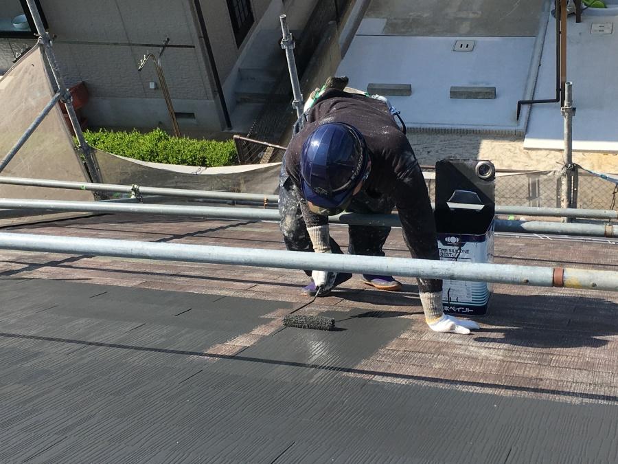 スレート屋根に足場を組んで塗料をローラーで塗布していく職人