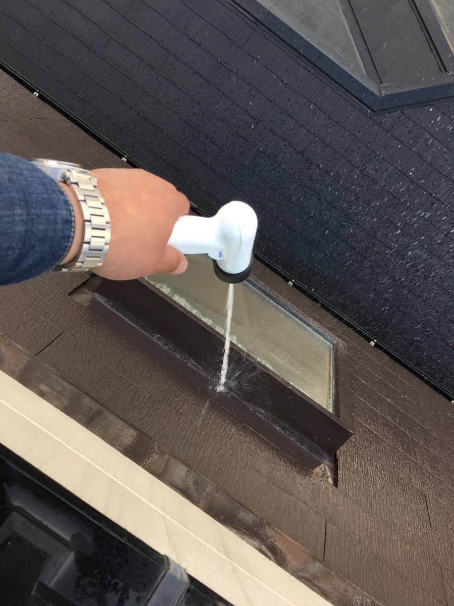 勾配屋根にある採光用の出窓に散水して雨水侵入の経路を調べる
