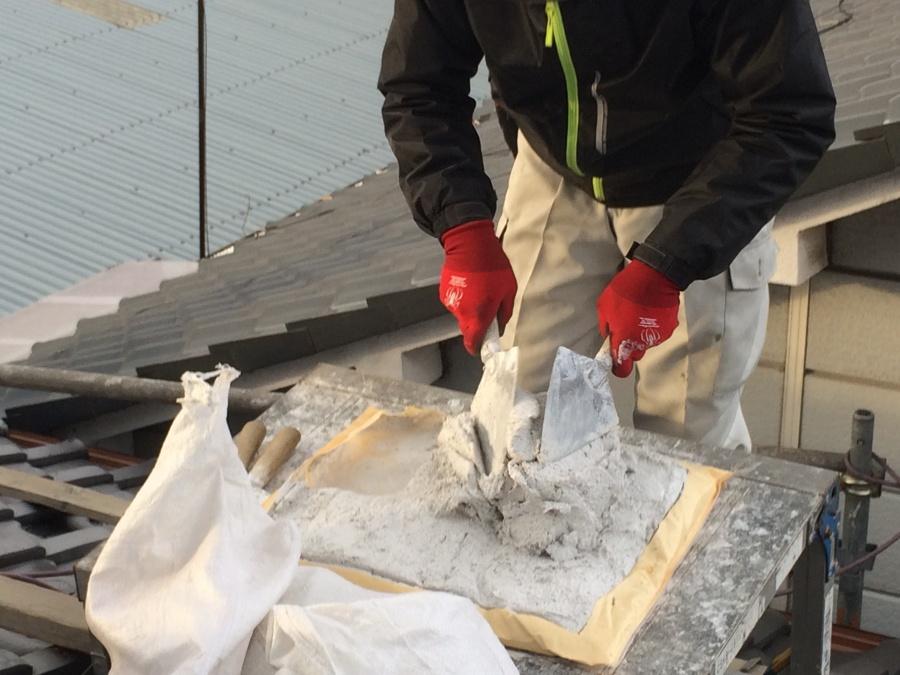屋根の上で漆喰を練る職人