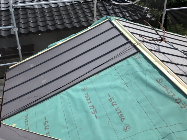 屋根葺き替え工事でガルバリウム鋼板を固定中