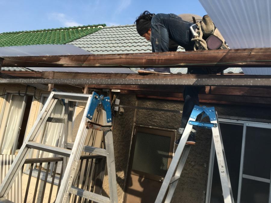 職人がベランダに新しいポリカーボネート製の屋根材を取り付けている様子