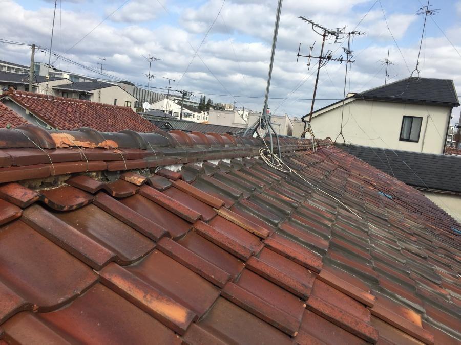 長屋造りのひと続きの劣化した瓦屋根の様子