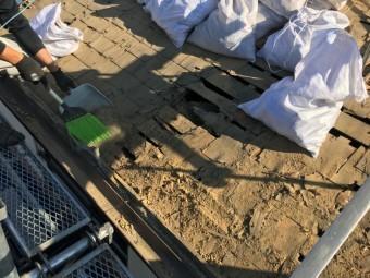 瓦の下の土を掃除し土嚢に入れて撤去する