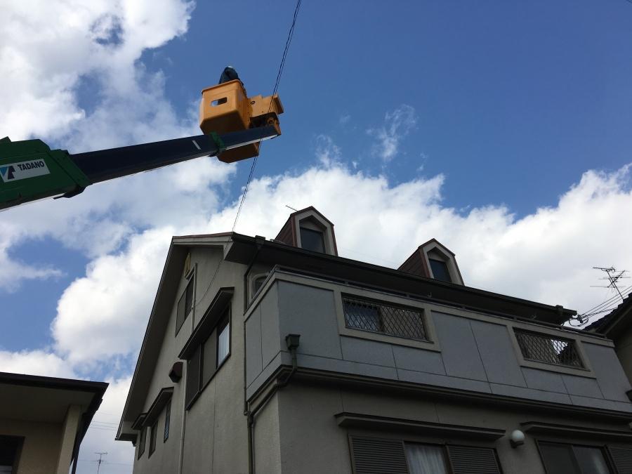 屋根点検のため高所作業者に乗る職人