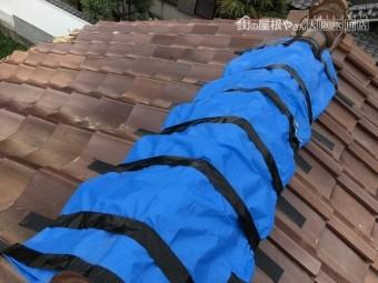 台風の被害を受けた屋根瓦にブルーシートで応急処置