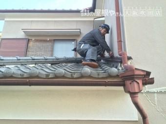 職人が屋根に上り瓦屋根と漆喰などの現地調査